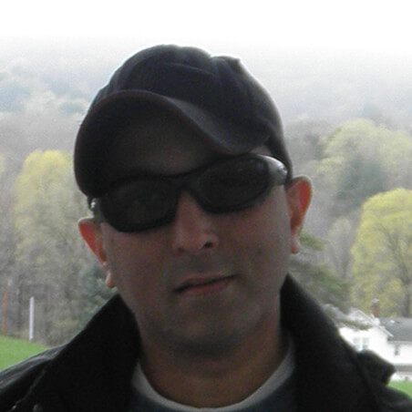 Headshot of Joel Isaac. He has a light skin tone and is wearing black sunglasses, a black cap, and black jacket.