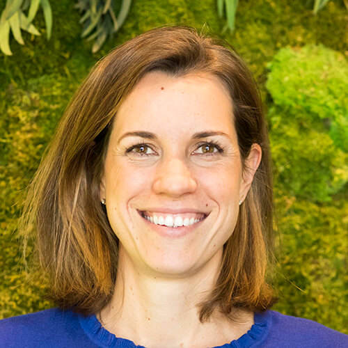 Headshot of Loi Goulet. She has a light skin tone, cropped brown hair, and wears a royal blue shirt. There is greenery behind her.