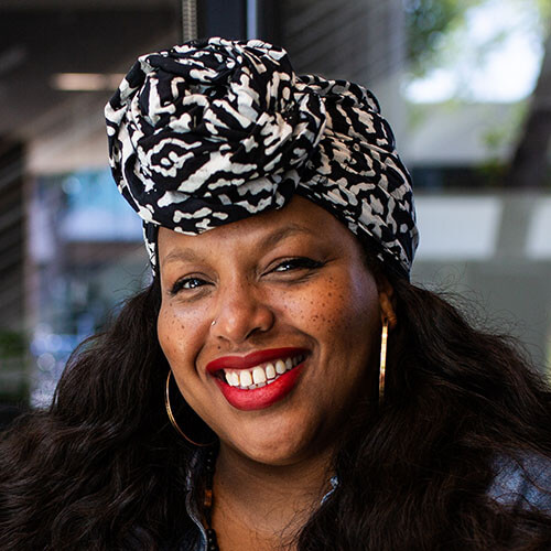 Headshot of Renee Reid. She has a dark skin tone, a black and white knotted headscarf, red lipstick, and gold hoop earrings.