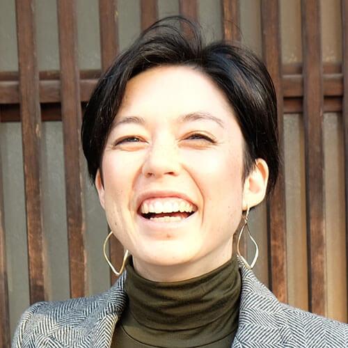 Headshot of Satsuko VanAntwerp. She has a light skin tone, big smile, short brown hair, and dangling earrings.