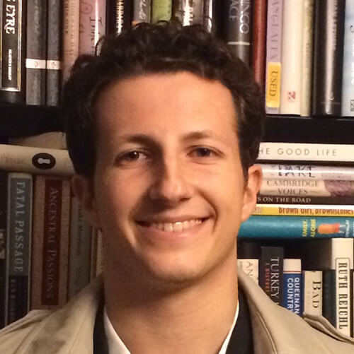 Headshot of Will Mongue. He has a light skin tone and curly, brown hair. There is a bookshelf directly behind him.